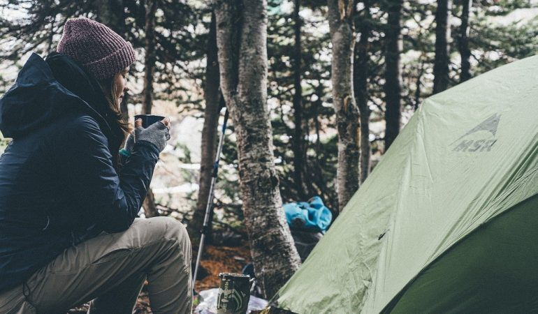 Camping avec femme devant une tente
